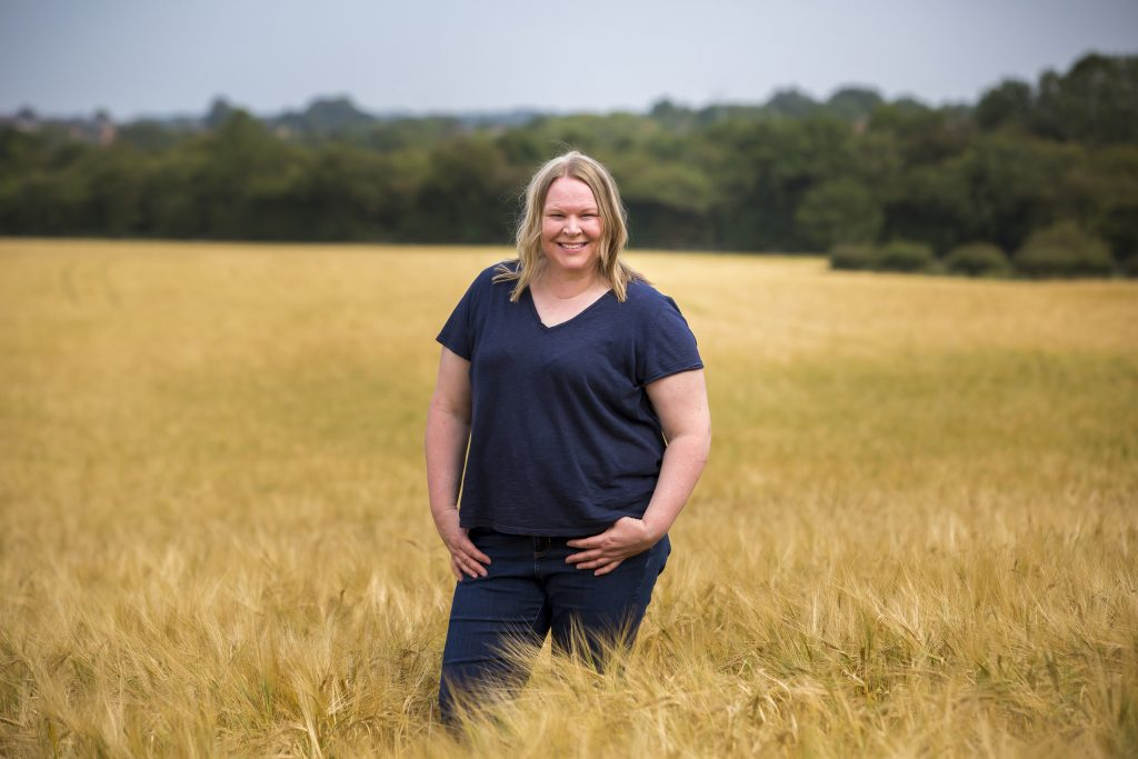 Farmer, Jo Martin standing in a field of spring barley